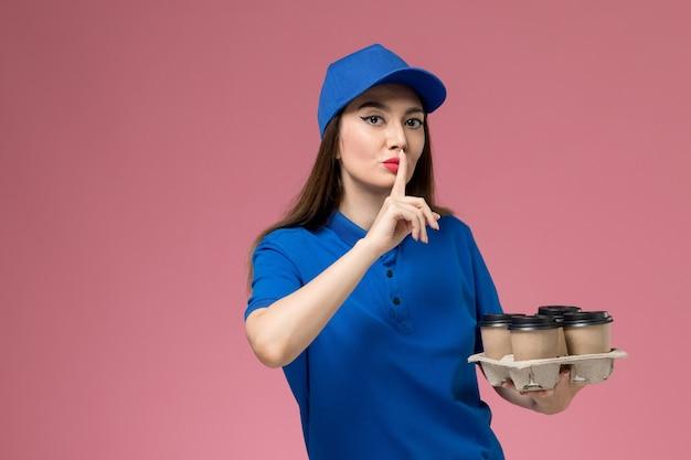 Weiblicher kurier der vorderansicht in der blauen uniform und im umhang, die kaffeetassen der lieferung halten und schweigenzeichen auf rosa wand zeigen