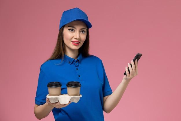 Weiblicher kurier der vorderansicht in der blauen uniform und im umhang, die kaffeetassen der lieferung unter verwendung ihres telefons auf rosa wand halten