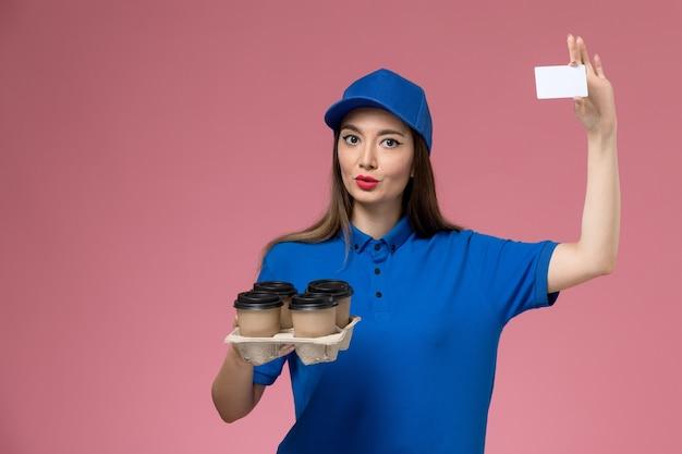 Weiblicher kurier der vorderansicht in der blauen uniform und im umhang, die kaffeetassen und weiße karte auf rosa wandarbeiter halten