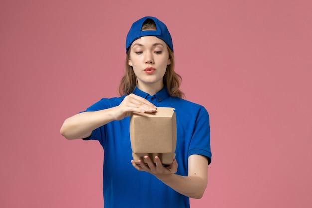 Weiblicher kurier der vorderansicht in der blauen uniform und im umhang, die kleine liefernahrungsmittelpakete an der rosa wand halten, dienstjobuniformdienstmitarbeiterarbeiter