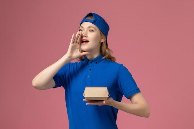 Weiblicher kurier der vorderansicht in der blauen uniform und im umhang, die kleines liefernahrungsmittelpaket auf dem arbeitsmädchenjob des rosa hintergrundlieferuniformdienstunternehmens halten