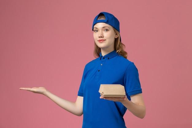 Weiblicher kurier der vorderansicht in der blauen uniform und im umhang, die kleines liefernahrungsmittelpaket auf dem rosa hintergrundlieferdienstfirmenarbeitsarbeitermädchenjob halten