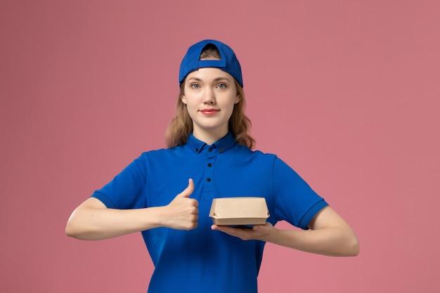 Weiblicher kurier der vorderansicht in der blauen uniform und im umhang, die kleines liefernahrungsmittelpaket auf dem rosa hintergrundlieferuniform-firmenarbeitsmädchenjob halten