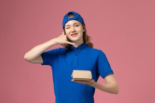 Weiblicher kurier der vorderansicht in der blauen uniform und im umhang, die kleines liefernahrungsmittelpaket auf dem rosa hintergrundlieferuniformuniversitätsarbeitsarbeitermädchenjob halten