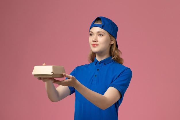 Weiblicher kurier der vorderansicht in der blauen uniform und im umhang, die kleines liefernahrungsmittelpaket auf dem rosa hintergrundlieferuniformuniversitätsarbeitsarbeitsarbeitermädchen halten