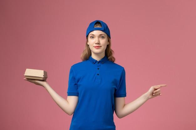 Weiblicher kurier der vorderansicht in der blauen uniform und im umhang, die kleines liefernahrungsmittelpaket auf rosa hintergrundjoblieferungsuniform-dienstleistungsunternehmen halten
