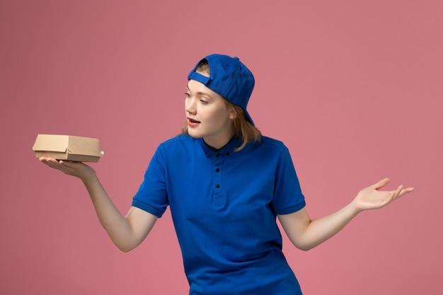 Weiblicher kurier der vorderansicht in der blauen uniform und im umhang, die kleines liefernahrungsmittelpaket auf rosa hintergrundjoblieferuniformuniversitätsarbeiterarbeiter halten