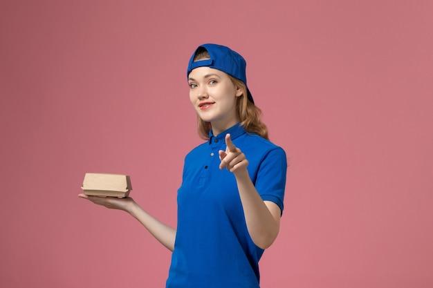 Weiblicher kurier der vorderansicht in der blauen uniform und im umhang, die kleines liefernahrungsmittelpaket auf rosa schreibtischjoblieferuniformuniversitätsarbeitsunternehmen halten