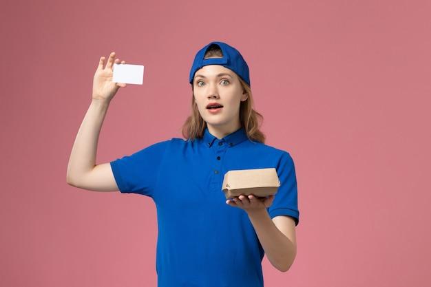 Weiblicher kurier der vorderansicht in der blauen uniform und im umhang, die kleines liefernahrungsmittelpaket mit karte auf rosa wand halten, lieferservice-mitarbeiterjob