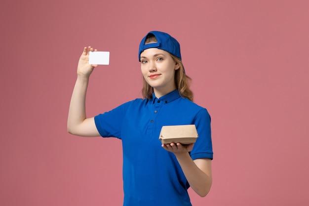 Weiblicher kurier der vorderansicht in der blauen uniform und im umhang, die kleines liefernahrungsmittelpaket mit karte auf rosa wand, lieferservice-mitarbeiter halten