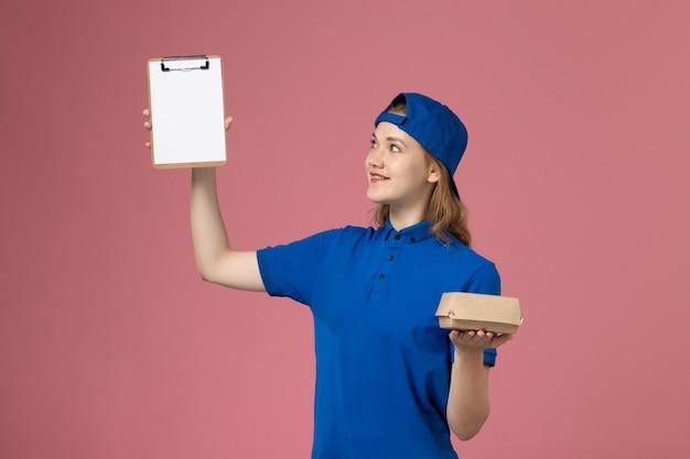 Weiblicher kurier der vorderansicht in der blauen uniform und im umhang, die kleines liefernahrungsmittelpaket und notizblock auf rosa wand halten, lieferservice-mitarbeiterarbeit