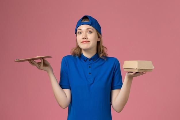 Weiblicher kurier der vorderansicht in der blauen uniform und im umhang, die kleines liefernahrungsmittelpaket und notizblock auf rosa wand halten, lieferservice-mitarbeiterarbeitsjob