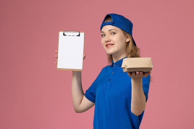 Weiblicher kurier der vorderansicht in der blauen uniform und im umhang, die kleines liefernahrungsmittelpaket und notizblock halten, die auf rosa wand lächeln, lieferservice-mitarbeiter