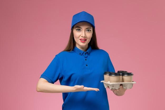 Weiblicher kurier der vorderansicht in der blauen uniform und im umhang, die lieferkaffeetassen auf hellrosa schreibtisch halten