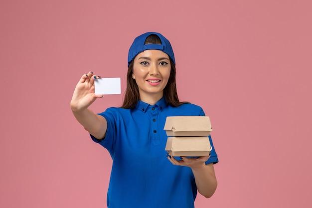 Weiblicher kurier der vorderansicht in der blauen uniformumhang-haltekarte und in den kleinen lieferpaketen lächelnd auf hellrosa wand, service-mitarbeiterzustellung