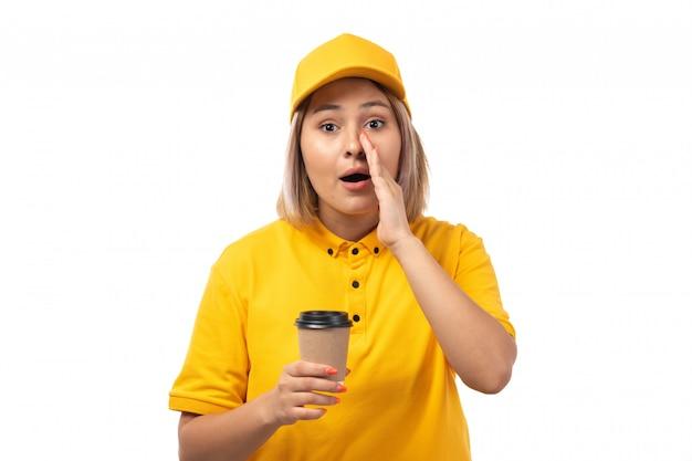 Weiblicher kurier der vorderansicht in der gelben kappe des gelben hemdes, die kaffeetasse auf weiß hält