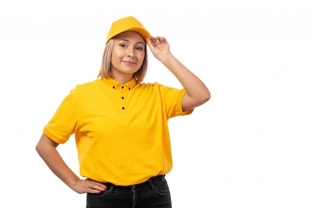Weiblicher kurier der vorderansicht in der gelben kappe des gelben hemdes lächelnd auf weiß