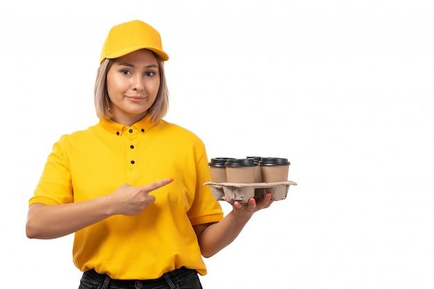 Weiblicher kurier der vorderansicht in der gelben kappe des gelben hemdes und der lächelnden schwarzen jeans, die kaffeetassen auf weiß halten
