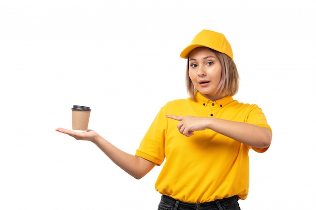 Weiblicher kurier der vorderansicht in der gelben kappe des gelben hemdes und der schwarzen jeans, die kaffeetasse auf weiß halten