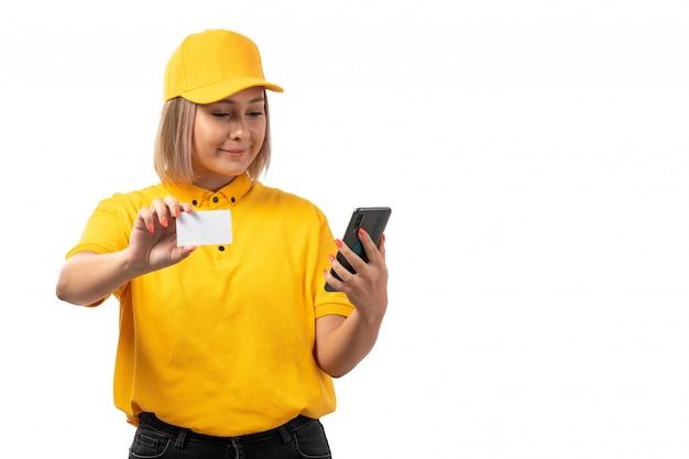 Weiblicher kurier der vorderansicht in der gelben kappe des gelben hemdes und der schwarzen jeans, die smartphone und weiße karte halten, die auf weiß lächeln