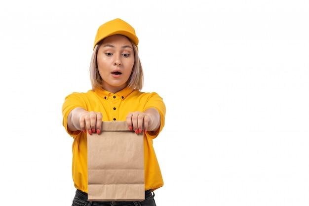 Weiblicher kurier der vorderansicht in der gelben kappe des gelben hemdes und in den schwarzen jeans, die nahrungsmittelpaket auf weiß halten