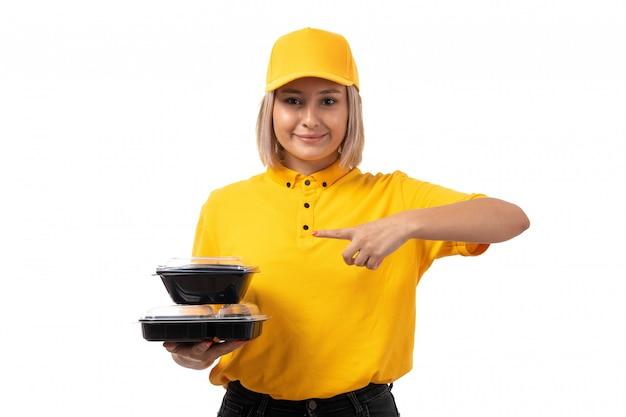 Weiblicher kurier der vorderansicht in der gelben kappe des gelben hemdes und in den schwarzen jeans, die schüsseln mit dem essen lächelnd auf weiß halten