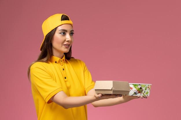 Weiblicher kurier der vorderansicht in der gelben uniform und im umhang, der lebensmittelpaket mit schüssel auf hellrosa wand liefert, dienstdienstuniformlieferung