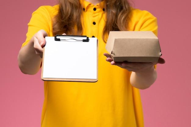 Weiblicher kurier der vorderansicht in der gelben uniform und im umhang, der notizblock des kleinen liefernahrungsmittelpakets auf rosa wand hält, servicejob-arbeitsuniform