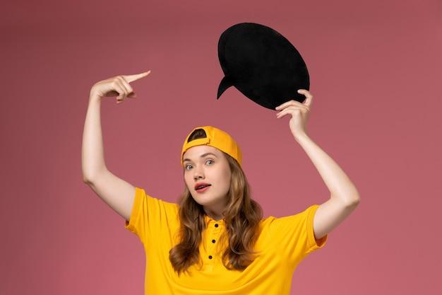 Weiblicher kurier der vorderansicht in der gelben uniform und im umhang, die großes schwarzes schild an der rosa wand halten, dienstdienstuniform der firma