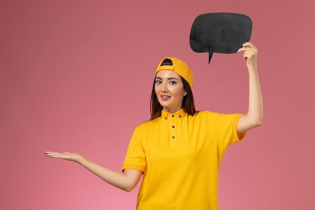 Weiblicher kurier der vorderansicht in der gelben uniform und im umhang, die großes schwarzes schild an der rosa wand halten, dienstuniform-auftragslieferung