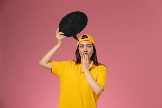 Weiblicher kurier der vorderansicht in der gelben uniform und im umhang, die großes schwarzes zeichen auf rosa wand halten, dienstuniform-lieferarbeiter-jobmädchen