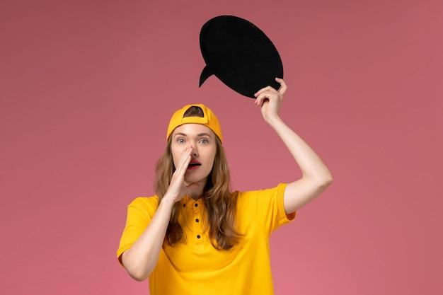 Weiblicher kurier der vorderansicht in der gelben uniform und im umhang, die großes schwarzes zeichen auf rosa wand halten, firmenservice-joblieferuniformuniformarbeiterin