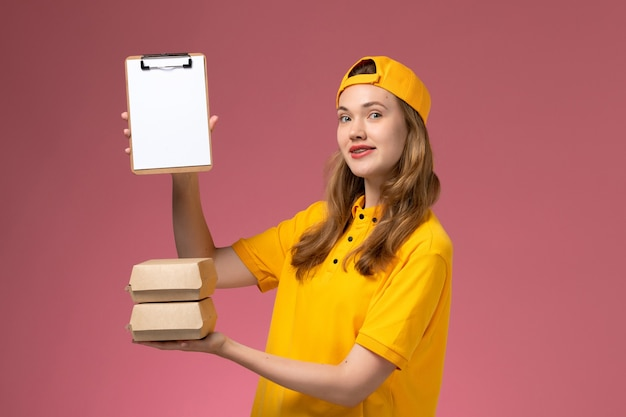 Weiblicher kurier der vorderansicht in der gelben uniform und im umhang, die kleine liefernahrungsmittelpakete mit notizblock auf rosa wanddienstjoblieferungsuniform halten