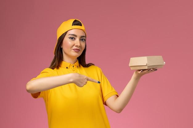 Weiblicher kurier der vorderansicht in der gelben uniform und im umhang, die kleines liefernahrungsmittelpaket auf dem mädchenjob der rosa wanduniformdienstlieferfirma halten