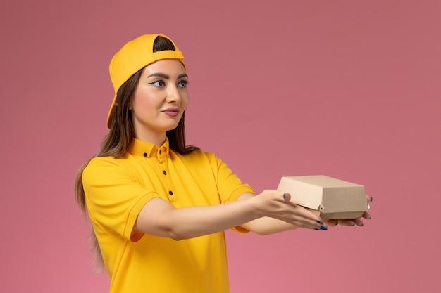 Weiblicher kurier der vorderansicht in der gelben uniform und im umhang, die kleines liefernahrungsmittelpaket auf der rosa wanduniform-dienstlieferungs-jobarbeiter halten