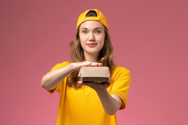 Weiblicher kurier der vorderansicht in der gelben uniform und im umhang, die kleines liefernahrungsmittelpaket auf hellrosa schreibtischdienstlieferuniformmädchenjob halten