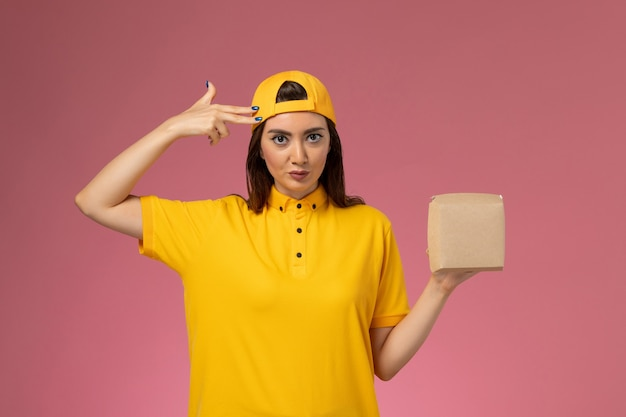 Weiblicher kurier der vorderansicht in der gelben uniform und im umhang, die kleines liefernahrungsmittelpaket auf hellrosa wanduniform-dienstlieferungs-arbeiterjob halten