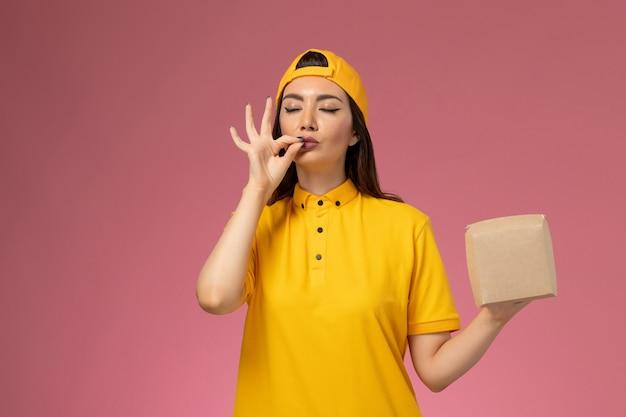 Weiblicher kurier der vorderansicht in der gelben uniform und im umhang, die kleines liefernahrungsmittelpaket auf hellrosa wanduniformdienstlieferungsmädchen halten