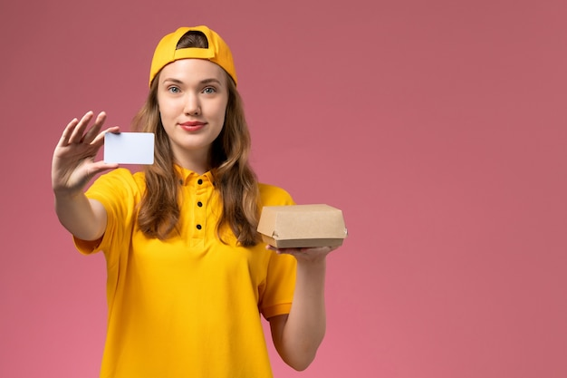 Weiblicher kurier der vorderansicht in der gelben uniform und im umhang, die kleines liefernahrungsmittelpaket und karte auf der rosa wanddienstjobarbeitslieferuniform halten