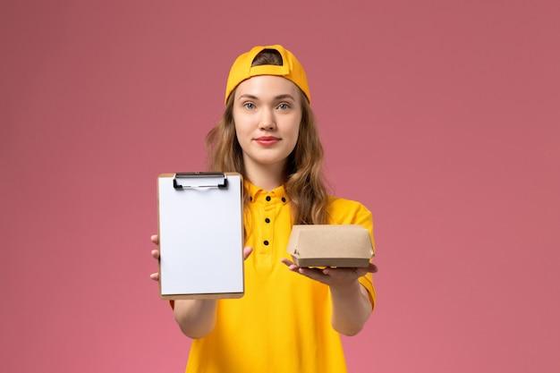 Weiblicher kurier der vorderansicht in der gelben uniform und im umhang, die kleines liefernahrungsmittelpaket und notizblock auf hellrosa wandservice-lieferuniform halten