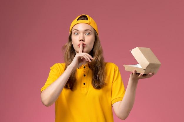 Weiblicher kurier der vorderansicht in der gelben uniform und im umhang, die leeres kleines liefernahrungsmittelpaket auf hellrosa wanddienstlieferuniformarbeiter halten