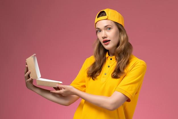 Weiblicher kurier der vorderansicht in der gelben uniform und im umhang, die leeres kleines liefernahrungsmittelpaket auf hellrosa wandservice-lieferarbeiteruniform halten