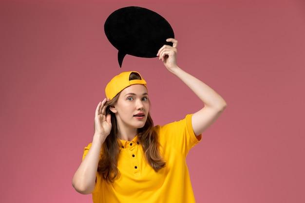 Weiblicher kurier der vorderansicht in der gelben uniform und im umhang, die schwarzes zeichen auf der rosa wandunternehmensdienstlieferuniformuniformmädchenarbeiterin halten
