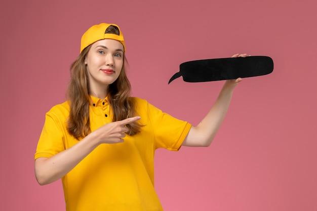 Weiblicher kurier der vorderansicht in der gelben uniform und im umhang, die schwarzes zeichen auf rosa dienstuniform-dienstleistungslieferauftrag der schreibtischuniform halten