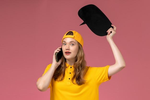 Weiblicher kurier der vorderansicht in der gelben uniform und im umhang, die schwarzes zeichen halten und am telefon auf der rosa wandfirma-dienstarbeiter-lieferuniform sprechen