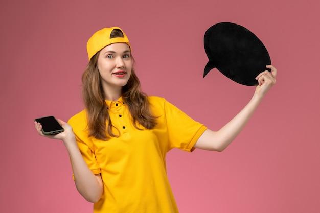 Weiblicher kurier der vorderansicht in der gelben uniform und im umhang, die schwarzes zeichen und smartphone auf rosa wandfirmenservicejoblieferuniform halten