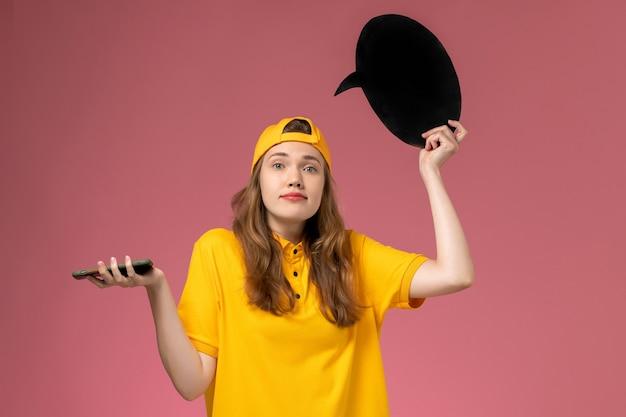 Weiblicher kurier der vorderansicht in der gelben uniform und im umhang, die schwarzes zeichen und smartphone auf rosa wandunternehmensdienstlieferungsuniform halten