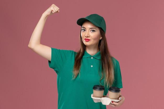 Weiblicher kurier der vorderansicht in der grünen uniform und im umhang, die lieferkaffeetassen auf rosa wandfirmenservicejobuniformlieferarbeiterin weibliches mädchen halten