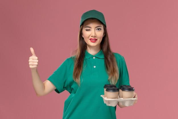 Weiblicher kurier der vorderansicht in der grünen uniform und im umhang, die lieferkaffeetassen halten, die auf rosa wanddienstuniform-lieferauftrag zwinkern
