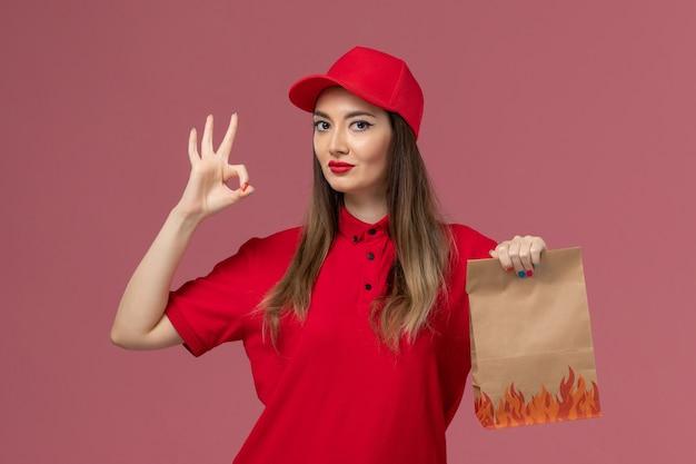 Weiblicher kurier der vorderansicht in der roten uniform, die papiernahrungsmittelpaket auf der hellrosa hintergrunddienstauftragslieferuniformfirma hält